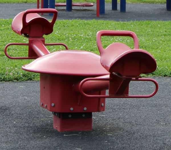 Absence Childrens Playground. Childs Red Seesaw. Close-up Day Empty Forshortened View. Grass Grassy Green Color Lawn Metal. No People Outdoors Park Playground Red Red Metal Seesaw. Red Seesaw. Seesaw.