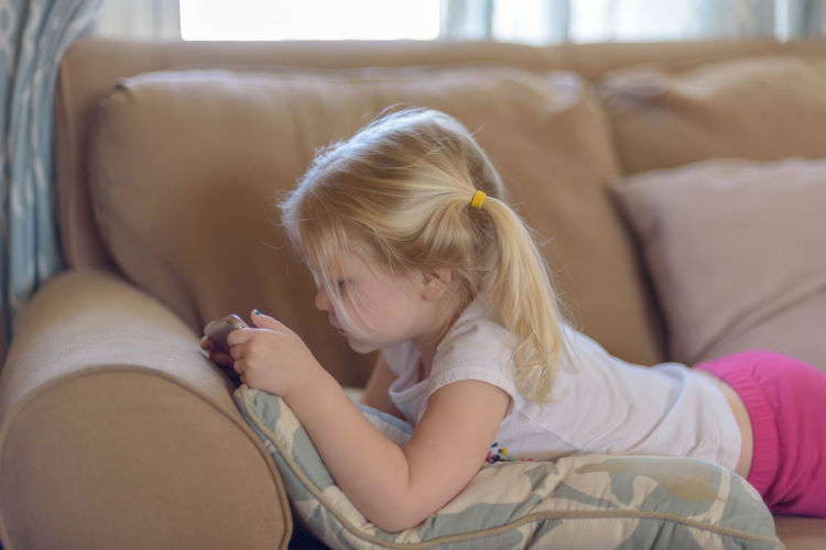 Preschool aged girl lying on her tummy on the couch watching a show on mobile device - kids using technology App Home Pigtails  Watching A Movie Child Family Life Homelife Internet Kid Kids At Home Kids Using Mobile Phones Kids Using Technology Little Girl Mobile Device On The Couch Preschooler Screen Time Smartphone Using Smartphone Using Technology Watching Tv Wifi Wireless Technology
