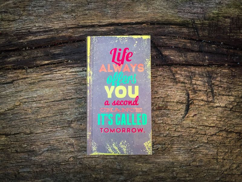 Motivational qoute on wooden table:Life always offers you a second chance it s called tomorrow Close-up Communication Wood - Material No People Outdoors Day Words Write Message Qoute  Motivational Life Book Calendars Notes Table Wood