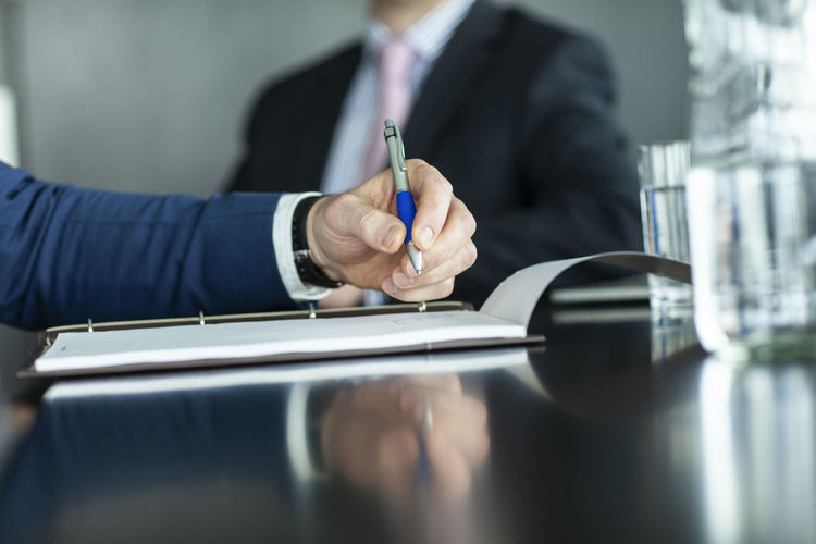 Midsection of businessman holding pen over paper by colleague in office