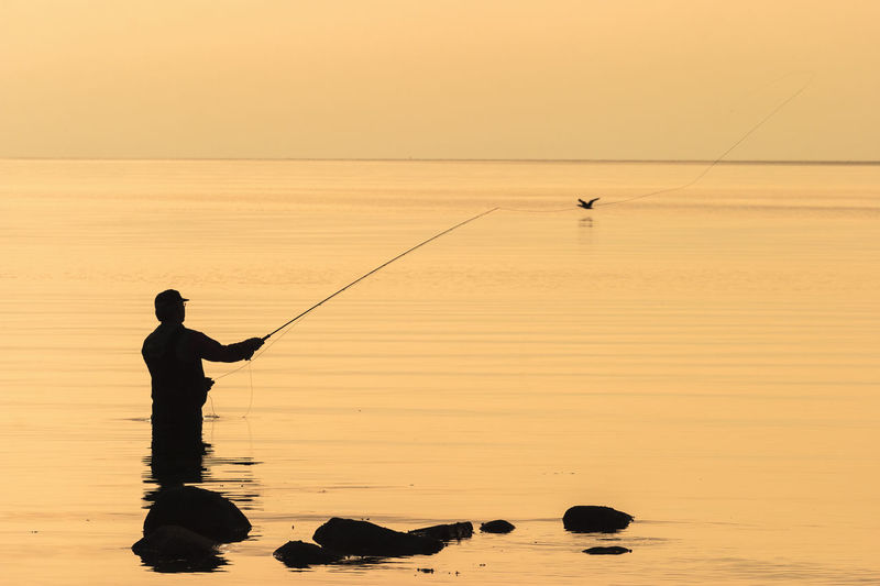 Sea fly fishing in the sunset at the sea