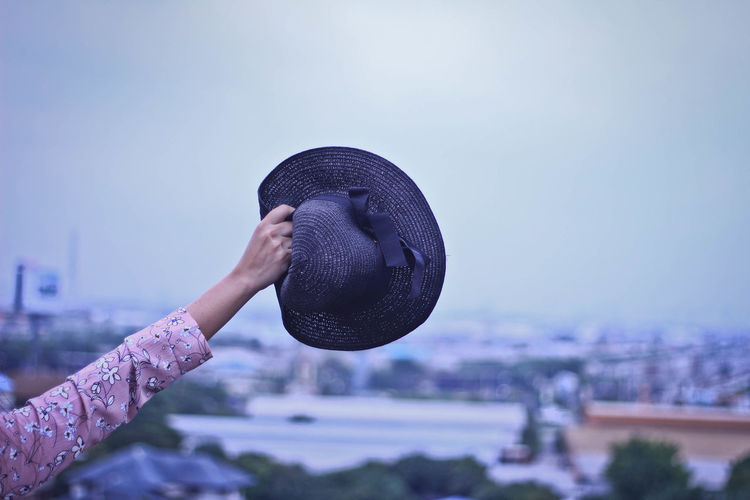 Close-up of person holding hat against sky