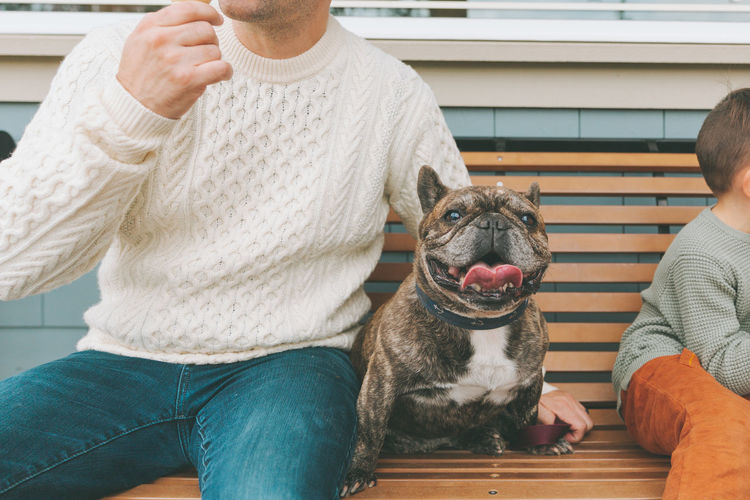 Midsection of man with dog sitting outdoors