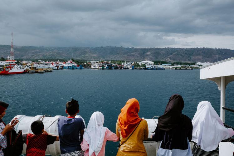 Rear view of people enjoying in sea against sky
