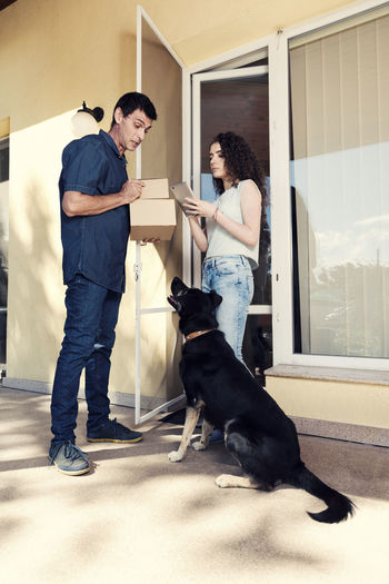 Woman signing on digital tablet while delivery man looking at dog against house