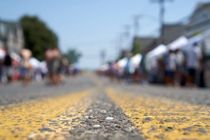 Low Angle View Road Architecture City Close-up Day Diminishing Perspective Direction Focus On Foreground Group Of People Incidental People Nature Outdoors Road Selective Focus Sky Sonyalpha Street Streetphotography Surface Level The Way Forward Transportation vanishing point Yellow