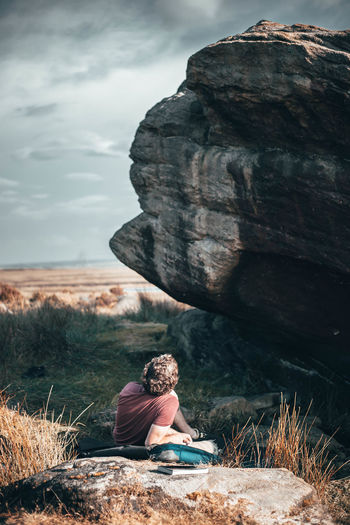 Man sitting on rock at shore against sky