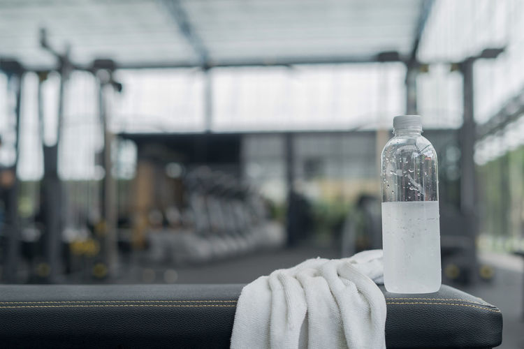 Close-up of water bottle and towel at gym