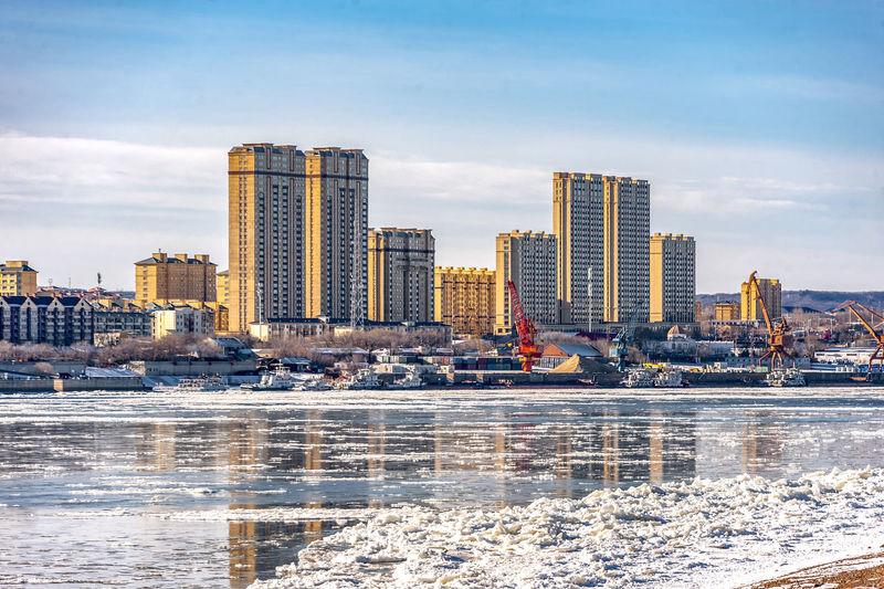 Modern buildings in city against sky during winter