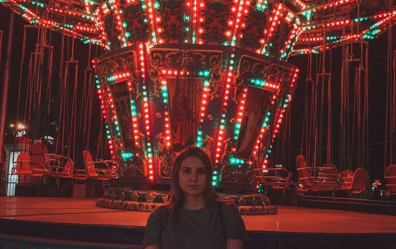 Portrait of woman in illuminated amusement park