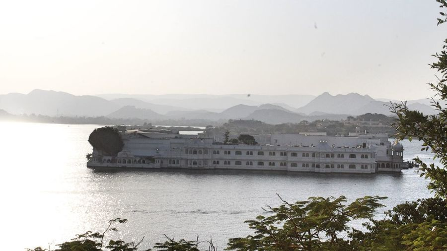 High view of Taj Lake Palace at Udaipur Lake Palace Udaipur Architecture Beauty In Nature Building Exterior Built Structure Clear Sky Day Lake Mountain Nature Nautical Vessel No People Outdoors Scenics Sky Taj Hotels Tranquility Transportation Tree Water Waterfront