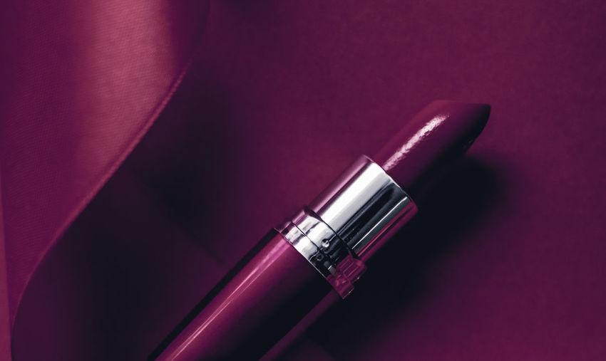 Close-up of lipstick over purple background