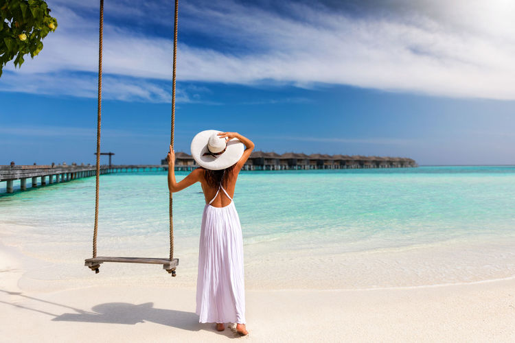 Attractive woman in white dress stands on a tropical beach near to a swing Maldives Tropics Woman Beach Hat Island Lifestyles Nature One Person Outdoors Real People Rear View Resort Sand Scenics Sea Sky Standing Sun Hat Sunny Swing Tranquil Scene Turquoise Vacations Water
