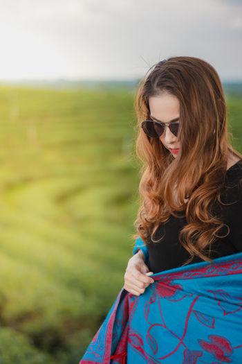 Beautiful woman wearing sunglasses on field