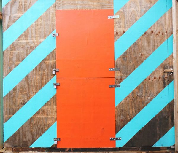 Close-Up Of Striped Wall With Closed Orange Door
