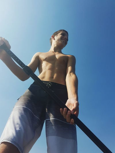 Low Angle View Of Shirtless Teenage Boy Holding Oar Against Clear Blue Sky