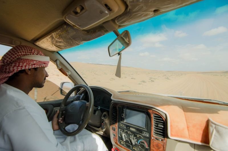 Man driving car on landscape against sky