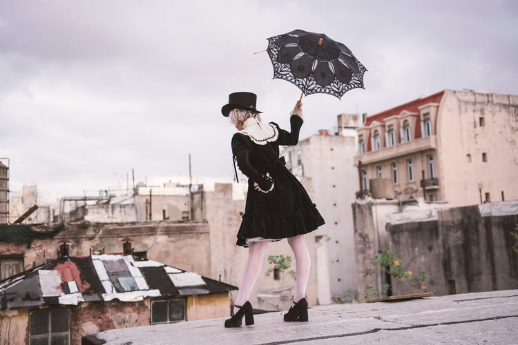 Man holding umbrella against sky in city