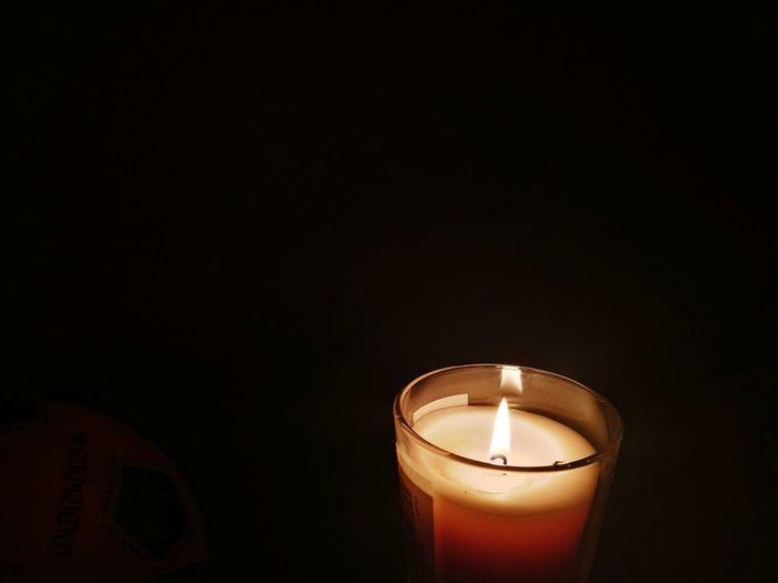 Close-up of illuminated candle against black background