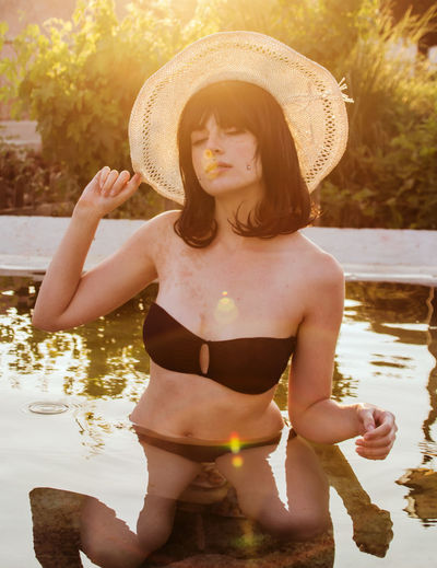 Beautiful Woman Beauty In Nature Day Front View Full Length Hat Leisure Activity Lifestyles Nature One Person Outdoors Real People Shirtless Standing Sunlight Tree Vacations Water Young Adult Young Women
