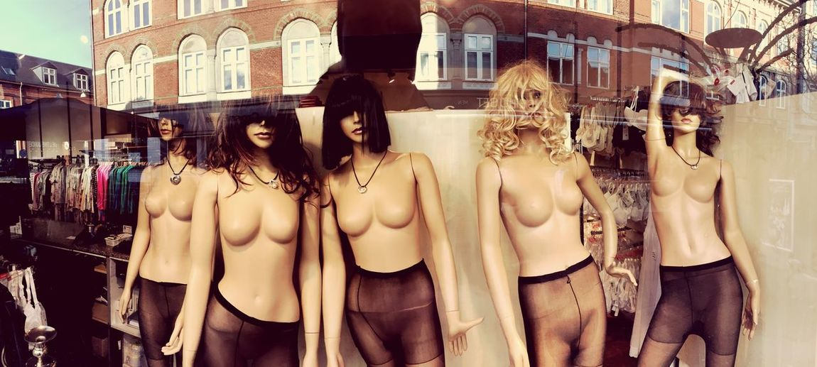 Mannequins In Store Seen Through Glass