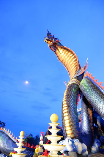 Low angle view of chinese dragon against blue sky