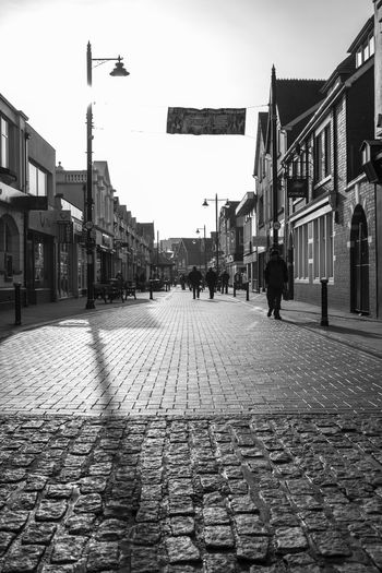 Low Angle View Porthcawl Shopping South Wales Street Lamp Architecture Blackandwhite Building Exterior Built Structure City Cobblestone Day Men Monochrome One Person Outdoors People Real People Road Sky Street The Way Forward Town Street Walking