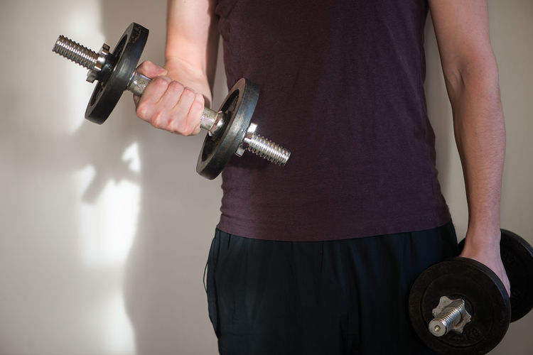 Midsection Of Man Exercising With Dumbbells