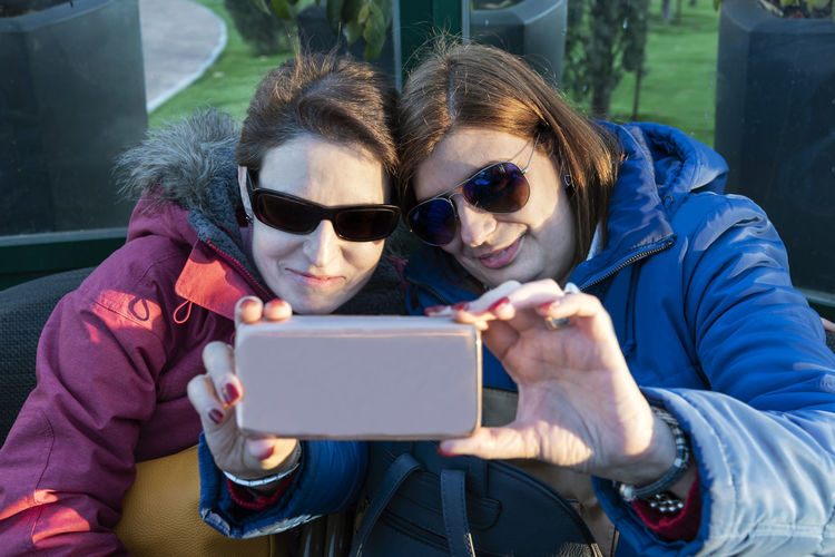 Two beautiful women taking a selfie with their mobile phone at sunset. Friendship concept. Two Women People person Friendship Friends Females Beautiful Sunglasses Sunset Outdoors Outside Sitting Background Wallpaper Copy Space Adult Cheerful Lifestyle Urban Life Casual Clothing Caucasian Brunette Red Blue Yellow Green Concept Mobile Phone Cellphone Smart Phone Selfie Portrait Device Technology Communication