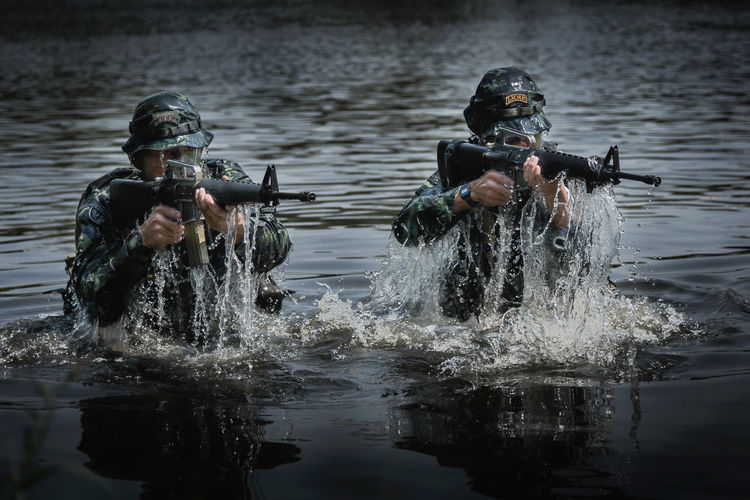 Two soldiers emerged from the water, ready to fire against the enemy Adult Day Group Of People Holding Lake Lifestyles Men Motion Nature Outdoors People Real People Reflection Splashing Sport Water Waterfront