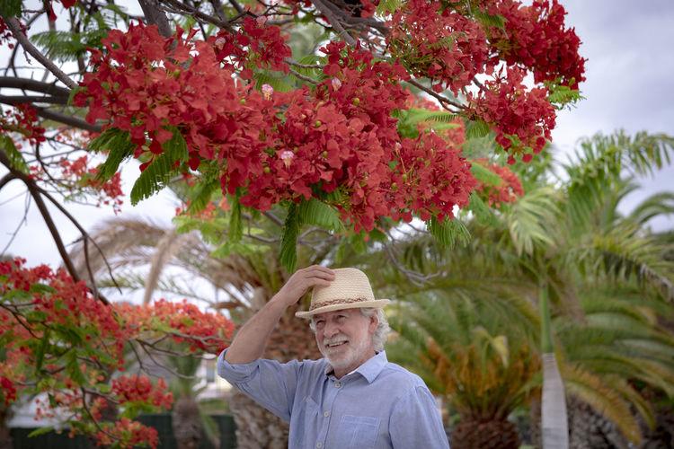 Smiling senior man wearing hat standing against flowering tree outdoors