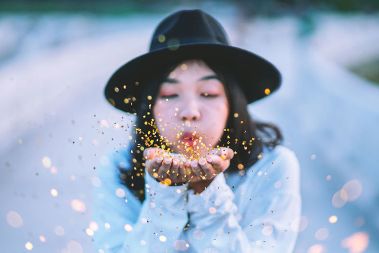 Young Woman Blowing Confetti During Winter