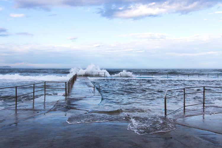 Waves Splashing On Pier Against Sky