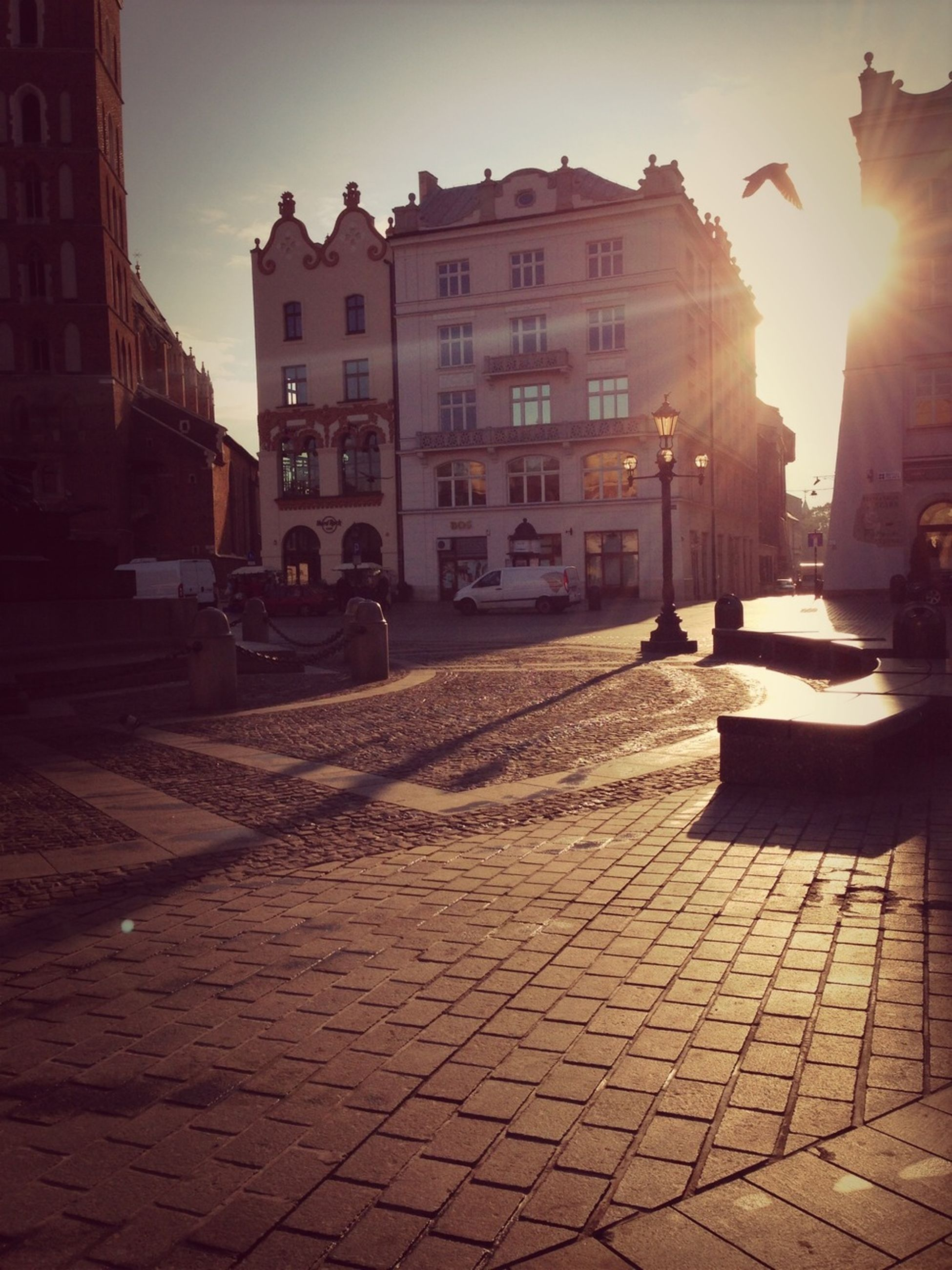 building exterior, architecture, built structure, sunlight, cobblestone, sun, street, sunbeam, lens flare, city, sidewalk, shadow, paving stone, incidental people, sunny, sky, outdoors, sunset, footpath, street light