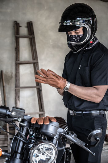 Man wearing gloves by motorcycle
