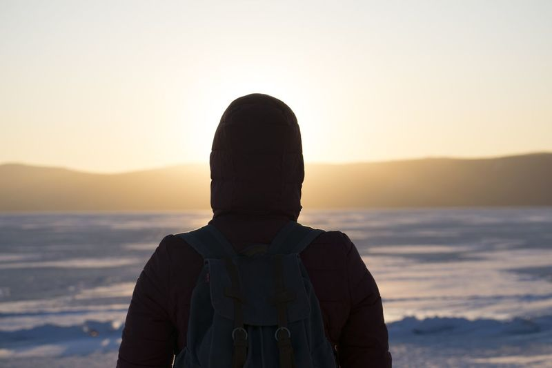 Rear view of man wearing hood while looking at sea against sky during sunset