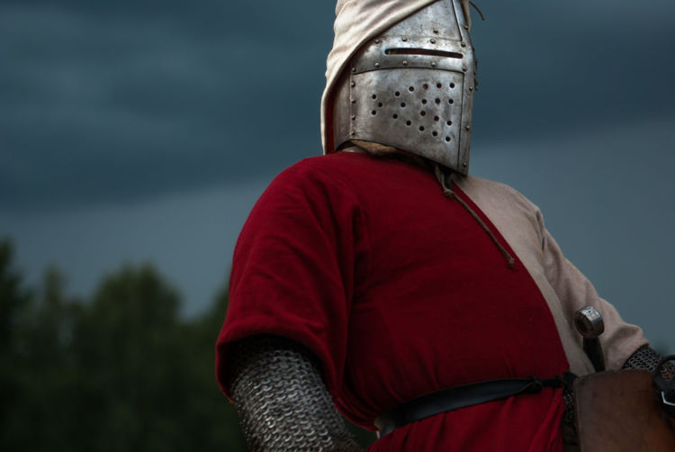 Low angle view of man wearing armored clothing against sky