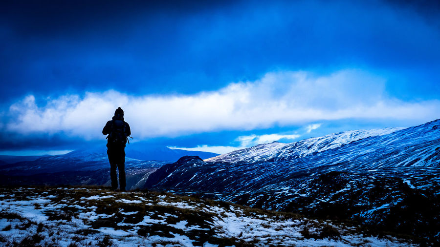 Rear view of silhouette man standing on snowcapped mountain against sky