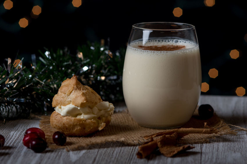 Glass of egg nog with a cream puff Christmas Cinnamon Cranberries Egg Nog Food And Drink Illuminated Milk Night Still Life Sweet Food Table