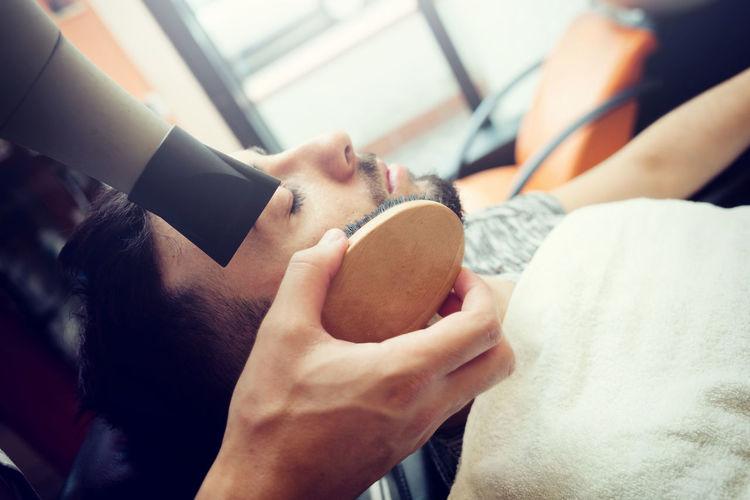Barber grooming customer at shop