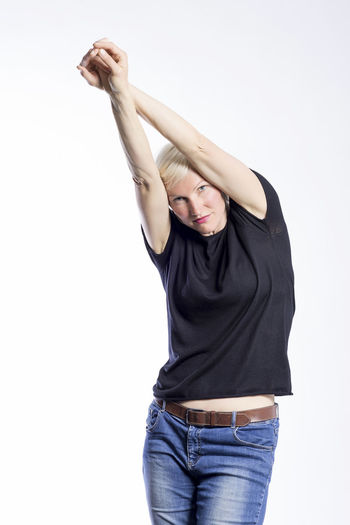 Portrait of a beautiful young blond woman modeling in a studio One Person Studio Shot White Background Three Quarter Length Casual Clothing Young Women Young Adult Front View Indoors  Cut Out Standing Lifestyles Women Arms Raised Beauty Human Arm Hair Fashion Beautiful Woman Hairstyle Jeans Teenager Females Modelling Model Blonde Girl Lady Looking At Camera Standing