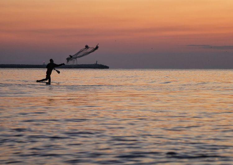 Silhouette fisherman fishing in sea against orange sky