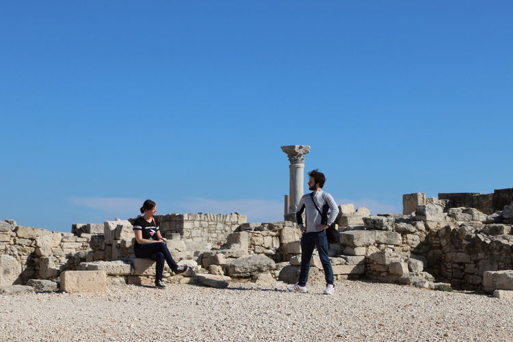 Couple looking at eachother against blue sky in limassol, cyprus.