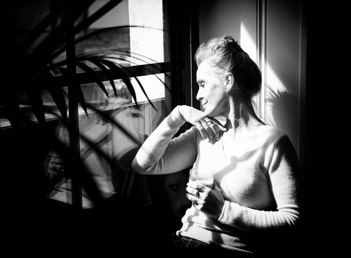 Young woman smoking cigarette while sitting in window