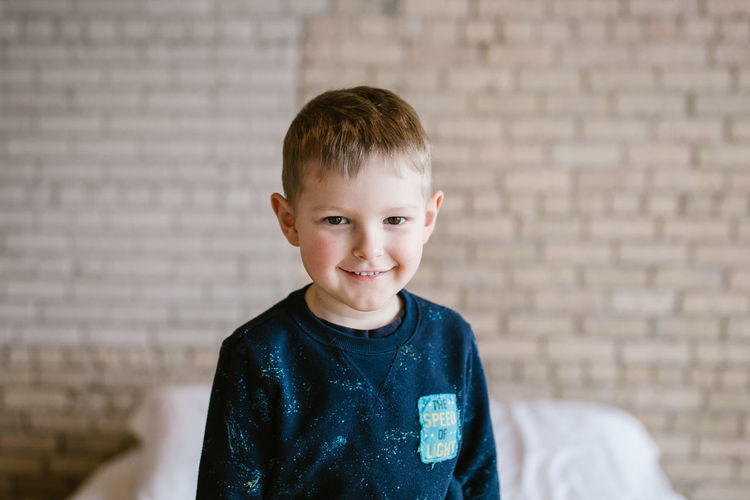 Portrait of smiling boy against brick wall at home