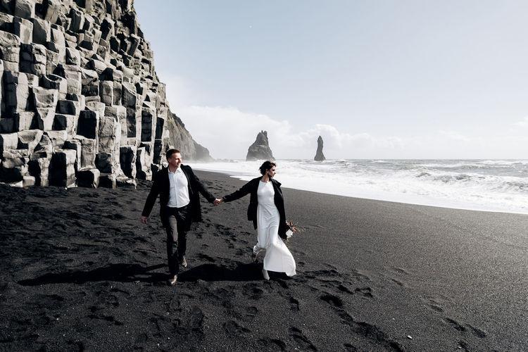 People walking on beach by sea against sky