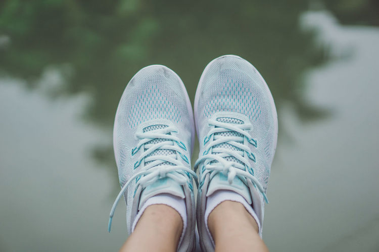 Low section of woman wearing shoes against lake
