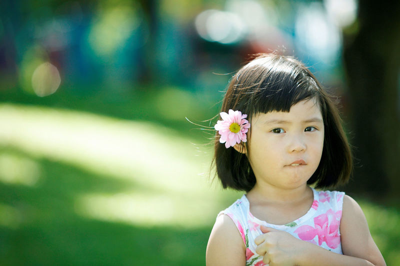 Close-up portrait of girl standing at park