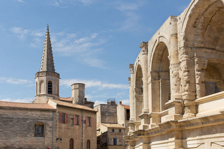 High section of the Arles Amphitheatre, a Roman arena. Ancient Arch Architecture Blue Building Exterior Built Structure Church Cloud Cloud - Sky Day Famous Place High Section History Low Angle View Old Ruin Outdoors Place Of Worship Religion Sky Spirituality The Past Tourism Tower Travel Destinations