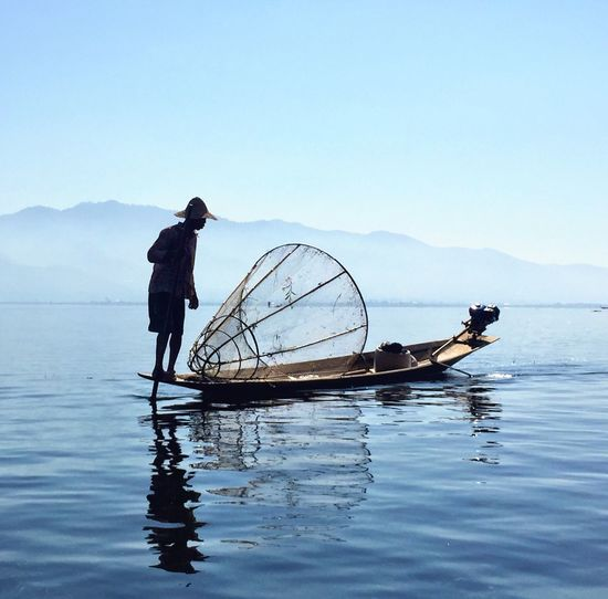 Fisherman with fishing net on boat in lake